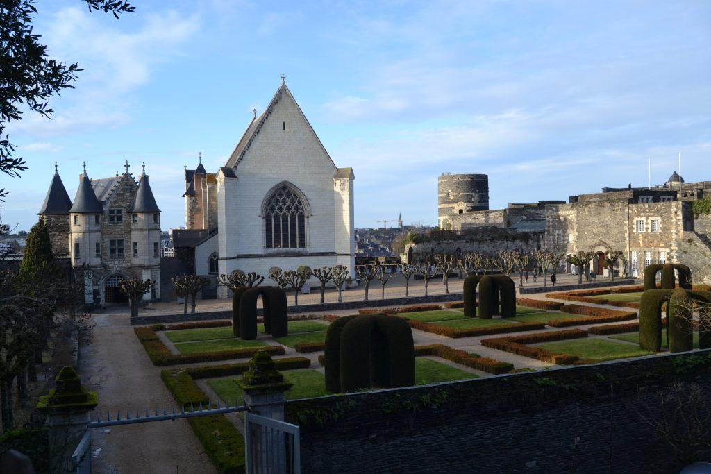 Photo des jardins à la française et de l'église à l'intérieur du château