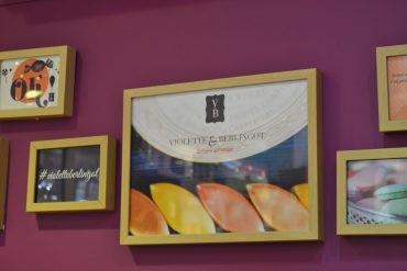Photo du mur derrière le comptoir de la boutique avec des affiches à l'effigie de Violette & Berlingot