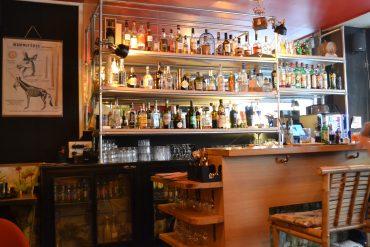 Photo du comptoir avec des chaises en bambou et un mur rempli de bouteilles