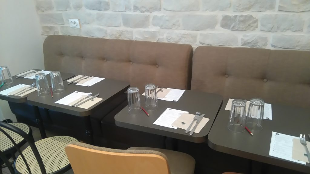 Photo de tables avec des banquettes d'un côté et des chaises de l'autre