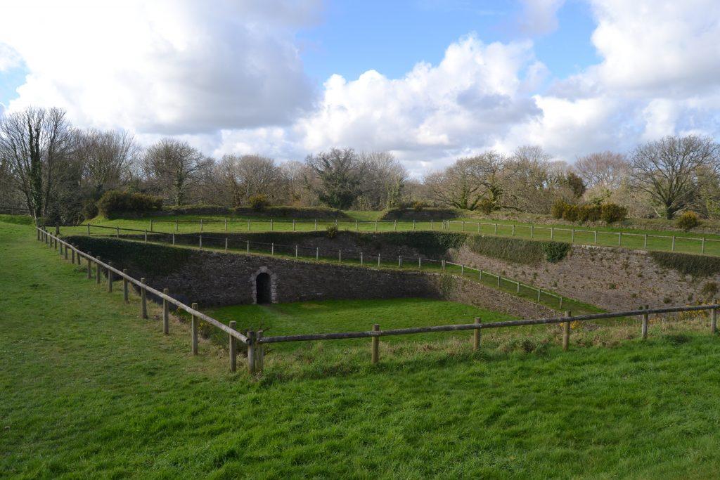 Photo de l'extérieur du fort avec une cour recouverte d'herbe en contre-bas