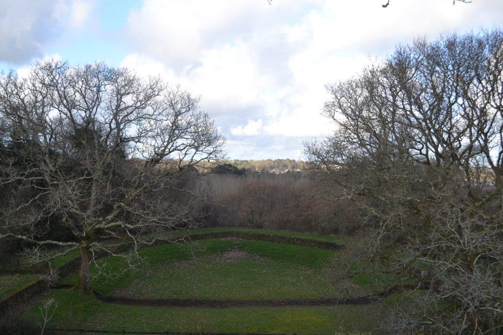 Photo d'une vue extérieure avec des arbres, de l'herbe et des murets en pierres