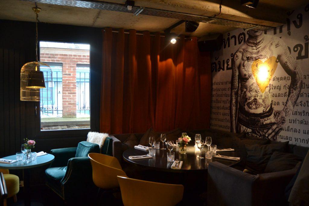 Photo de la salle avec une photo d'un torse d'homme tatoué sur un mur et des rideaux rouges