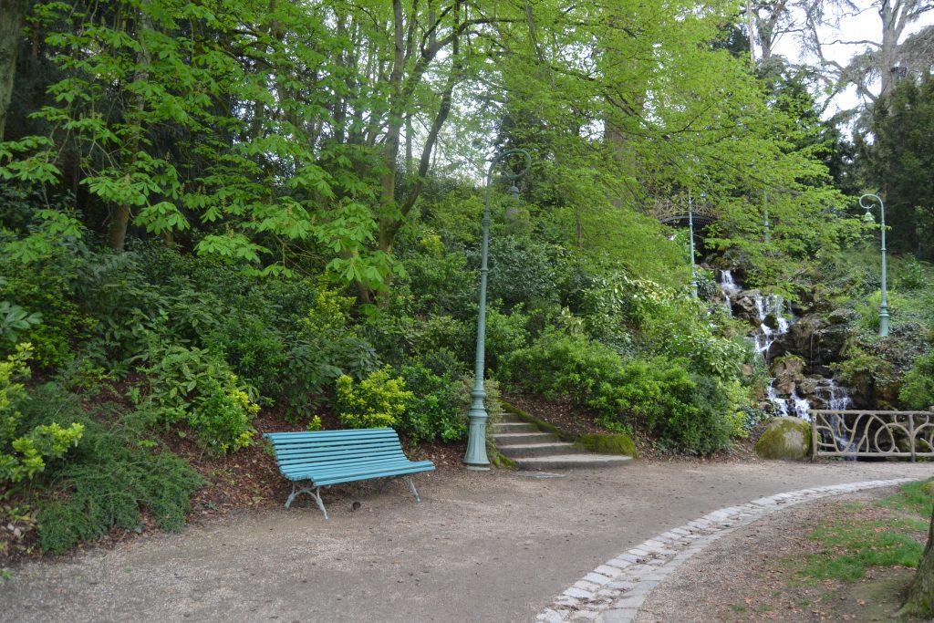Photo d'un banc vert sur le bord d'un chemin