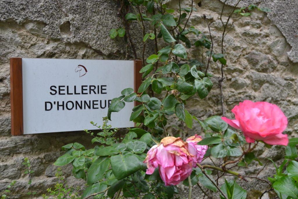 """Photo de l'écriteau """"Sellerie d'honneur"""" sur un mur de pierre, derrière des roses roses"""