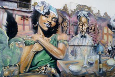 Phot d'un tag où l'on voit plusieurs personnages dont une femme noire avec un haut vert et un bandeau dans les cheveux