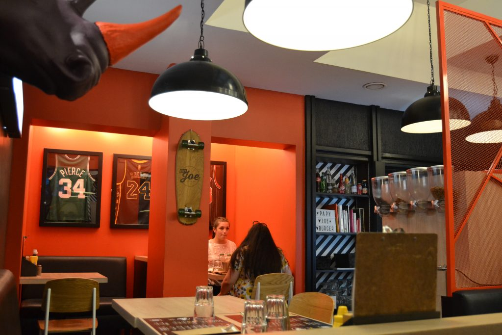 Photo de la salle, avec les murs peint en orange ou noir, avec trois jerseys encadrés au mur ainsi qu'une planche de skate