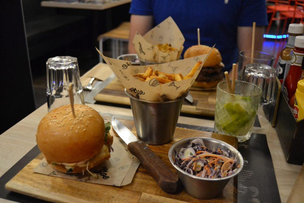 Photo du burger The Little Italy sur la planche de bois de service, sur la droite le pot de coleslaw et de frites prise de plus loin que la première