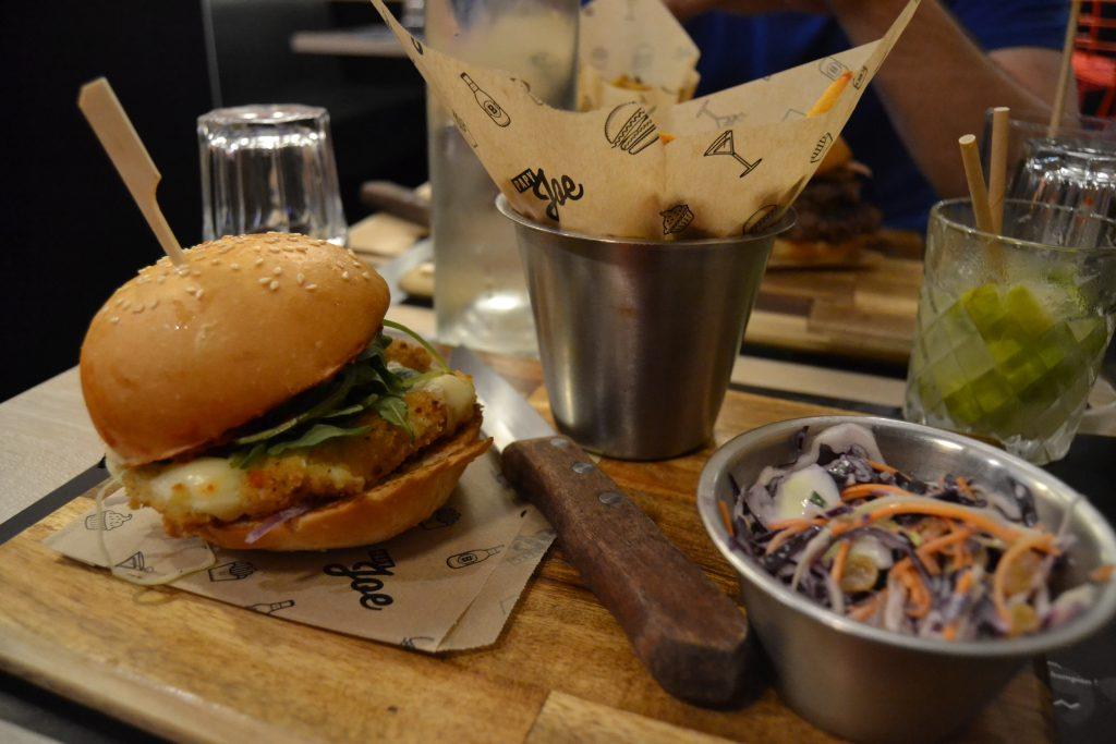 Photo du burger The Little Italy sur la planche de bois de service, sur la droite le pot de coleslaw et de frites